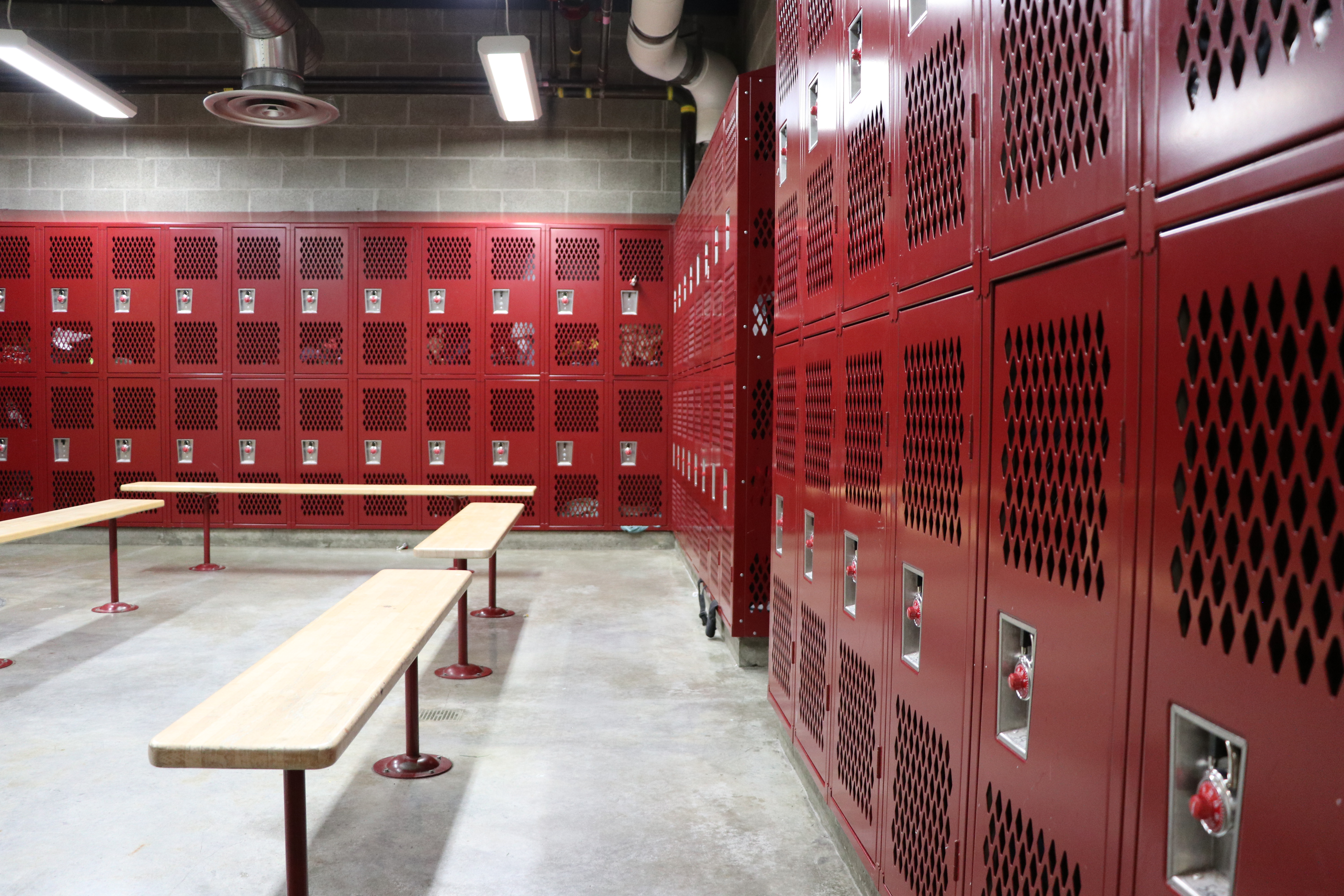 Empty locker room, red lockers and benches.