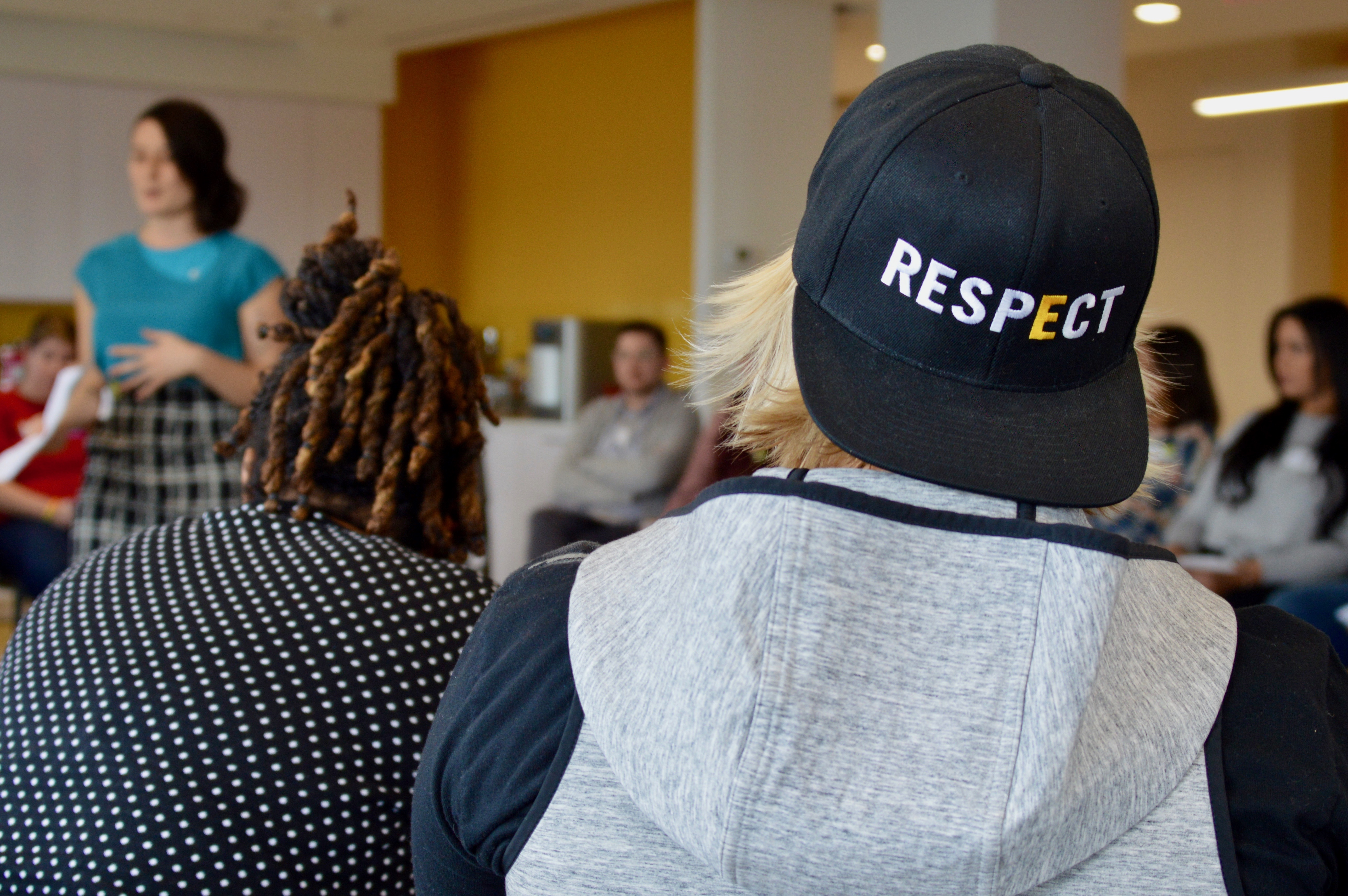 A blond adult volunteer with their back to the camera attends the 2019 NYC Training of Trainers. They wear a GLSEN black snapback with the text: RESPECT. They sit with several other volunteers in a U-shape of chairs listening to a standing GLSEN National staff member in a blue shirt.
