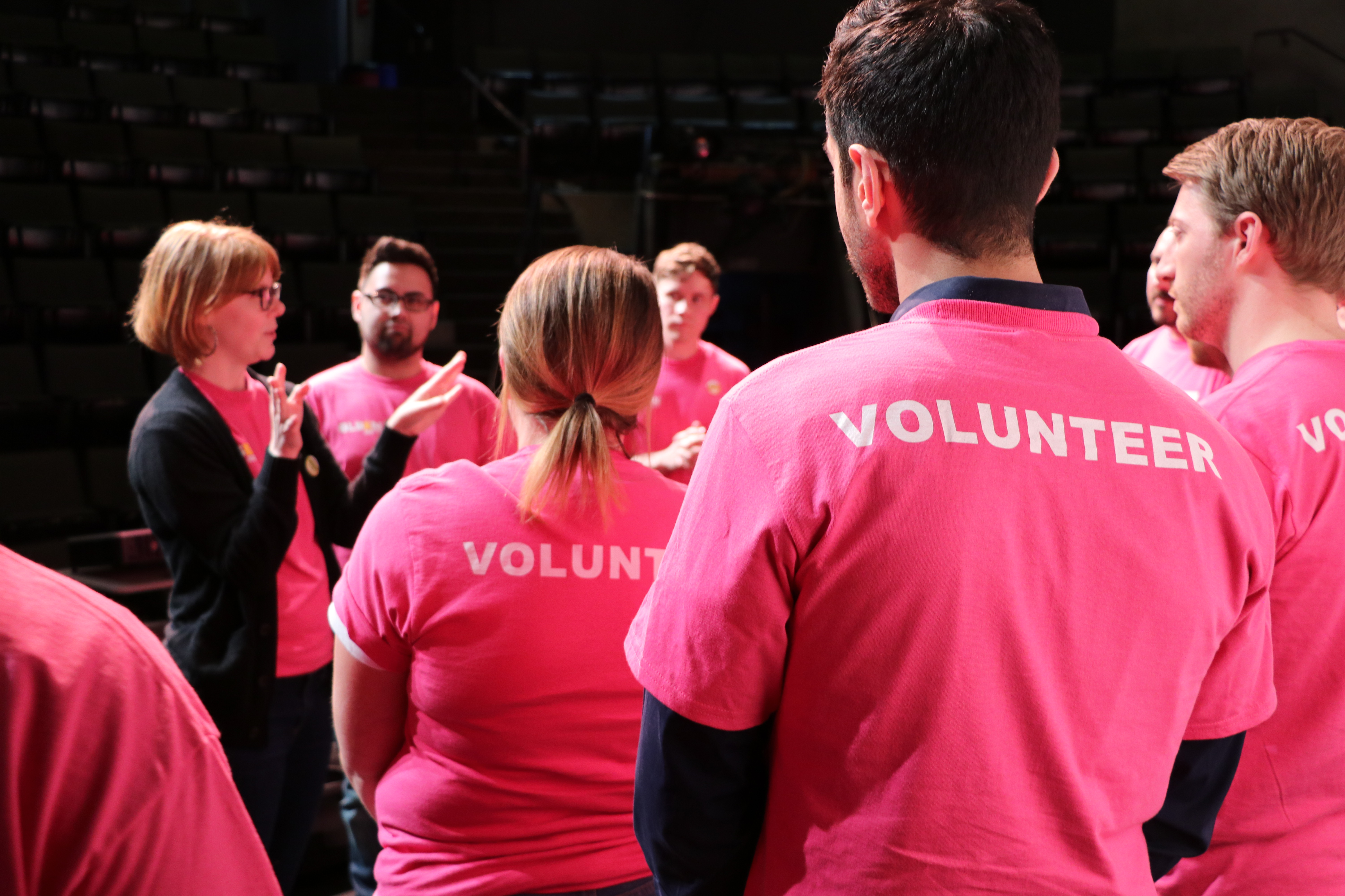 At a GLSEN Greater Cincinatti event, several adult volunteers in pink shirts circle around a speaking volunteer in a black cardigan. The back of the pink shirts reads: VOLUNTEER.