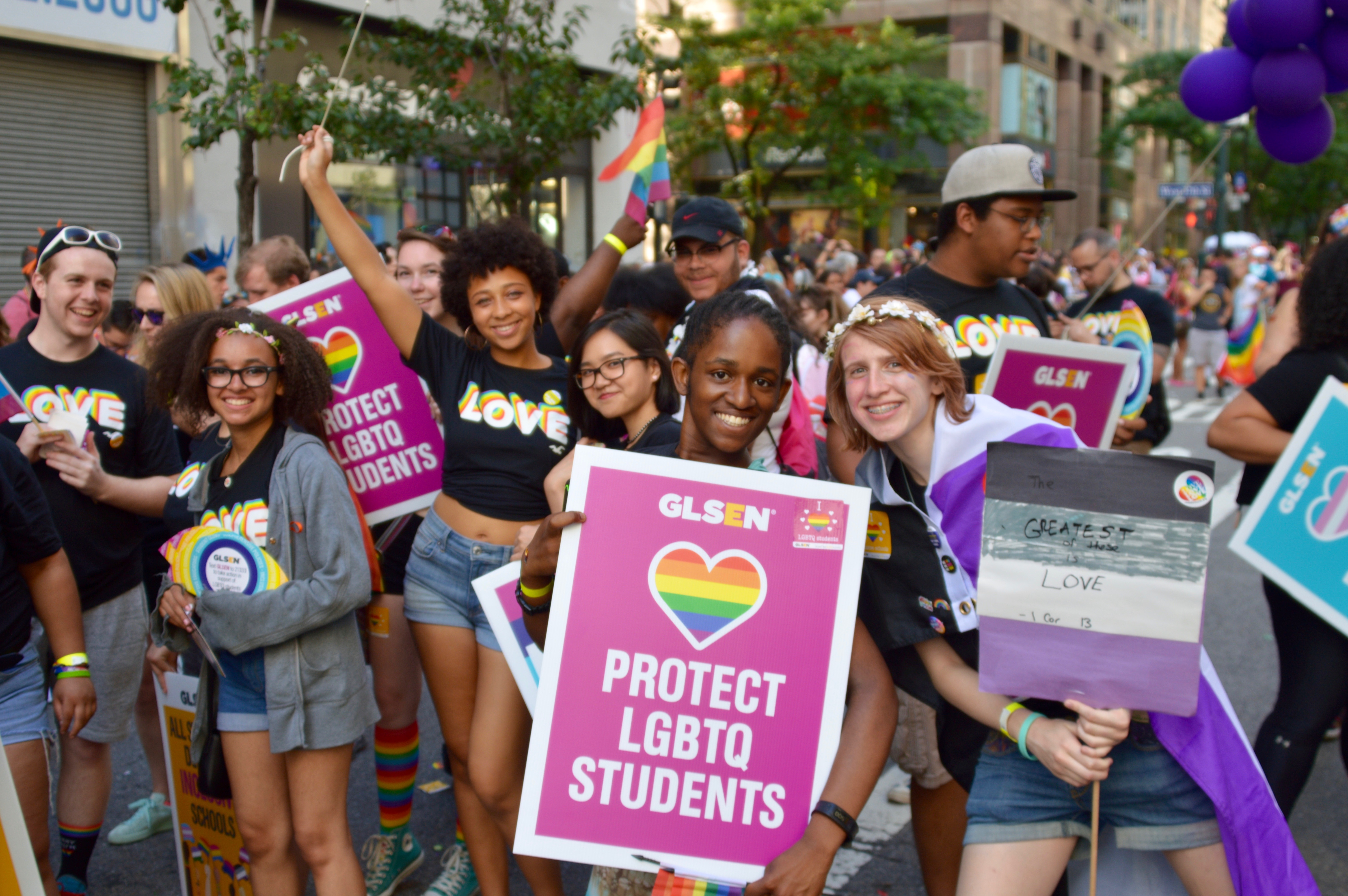 A group of student vounteers smile at the camera while marching in the 2018 NYC Pride March. They wear GLSEN Love shirts and hold up GLSEN posters that read: Protect LGBTQ Students.