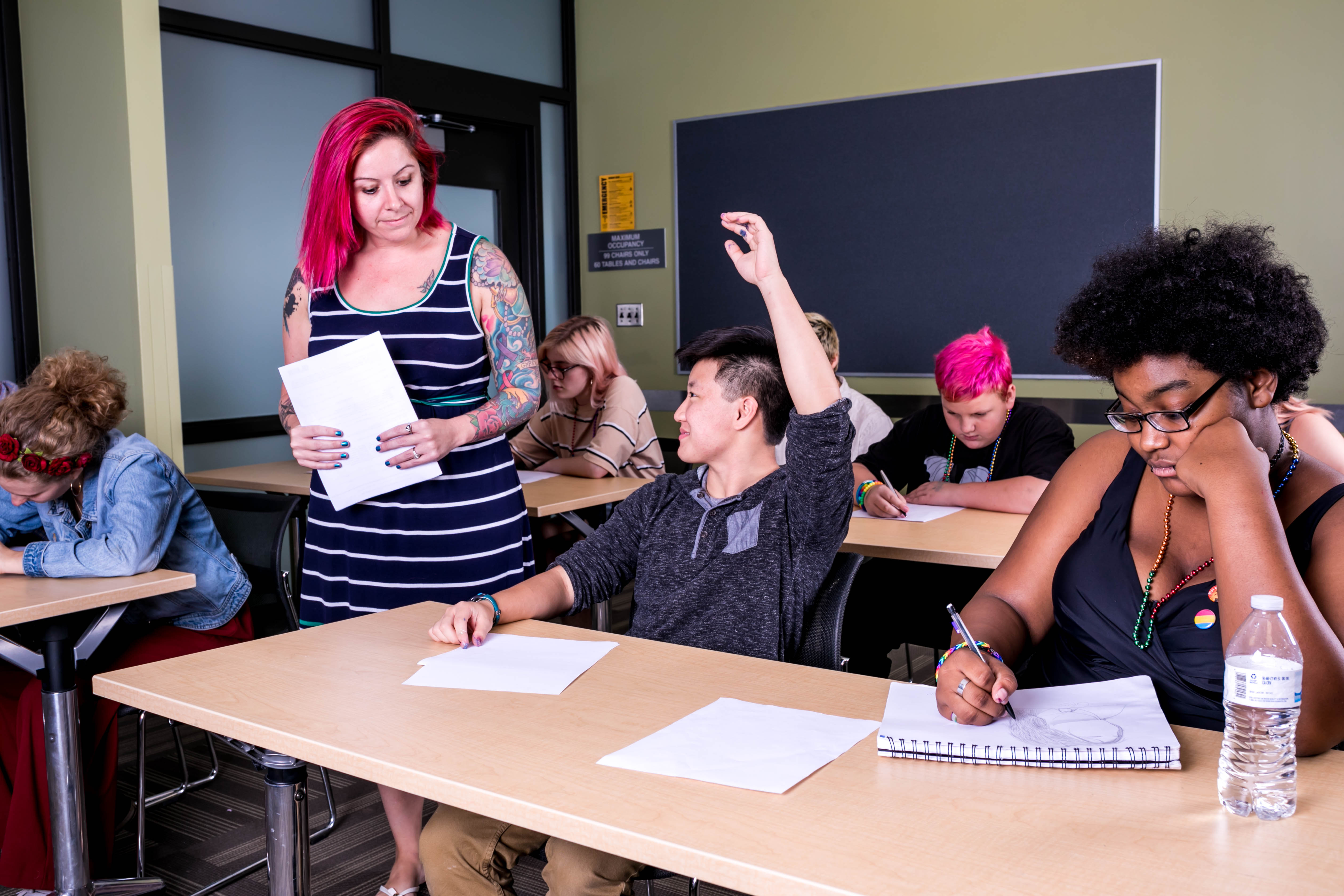 Four classroom tables of students write in their notebooks. A pink-haired educator holding papers approaches a student with their hand raised.
