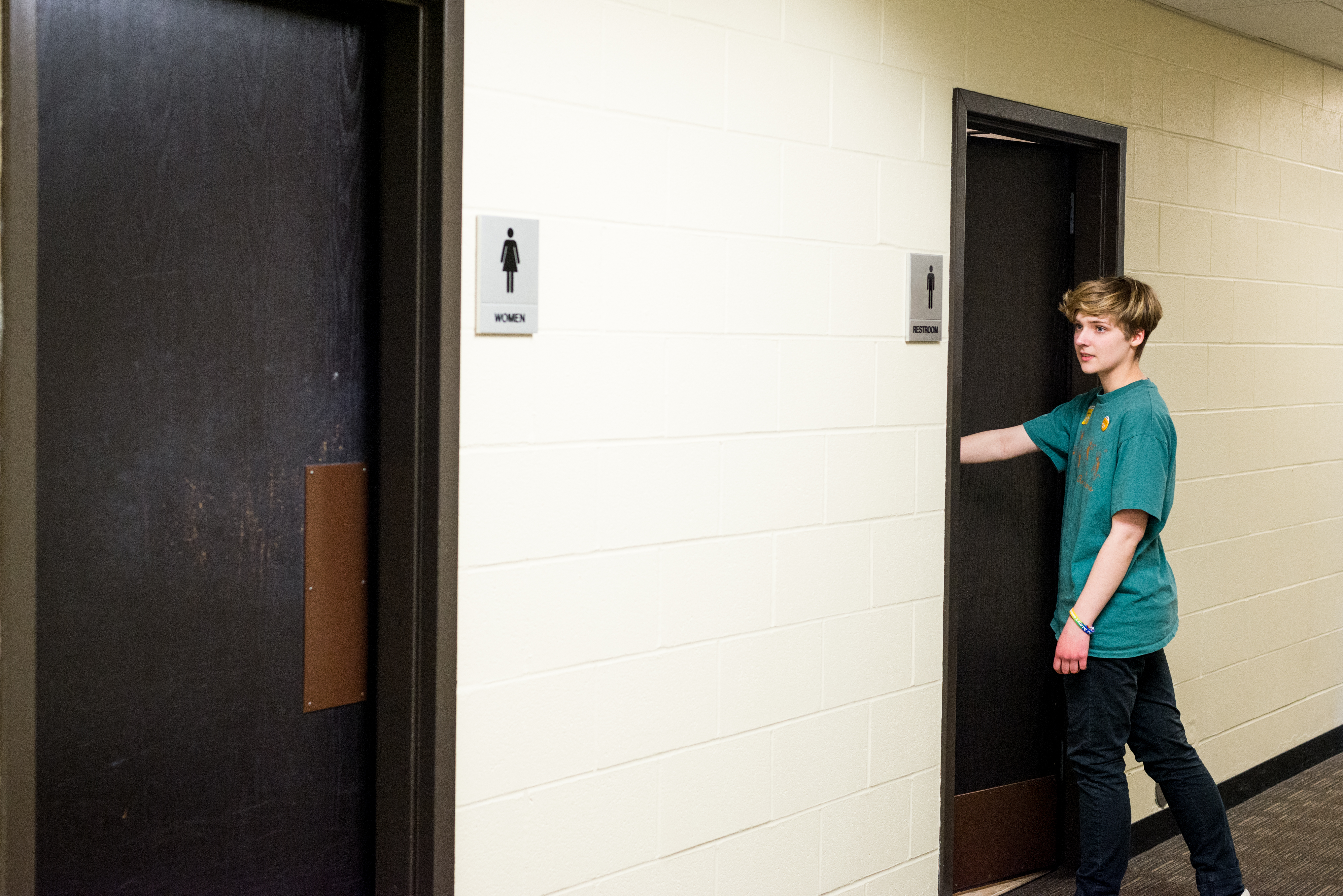 Student entering a men's restroom while looking at the women's restroom sign.