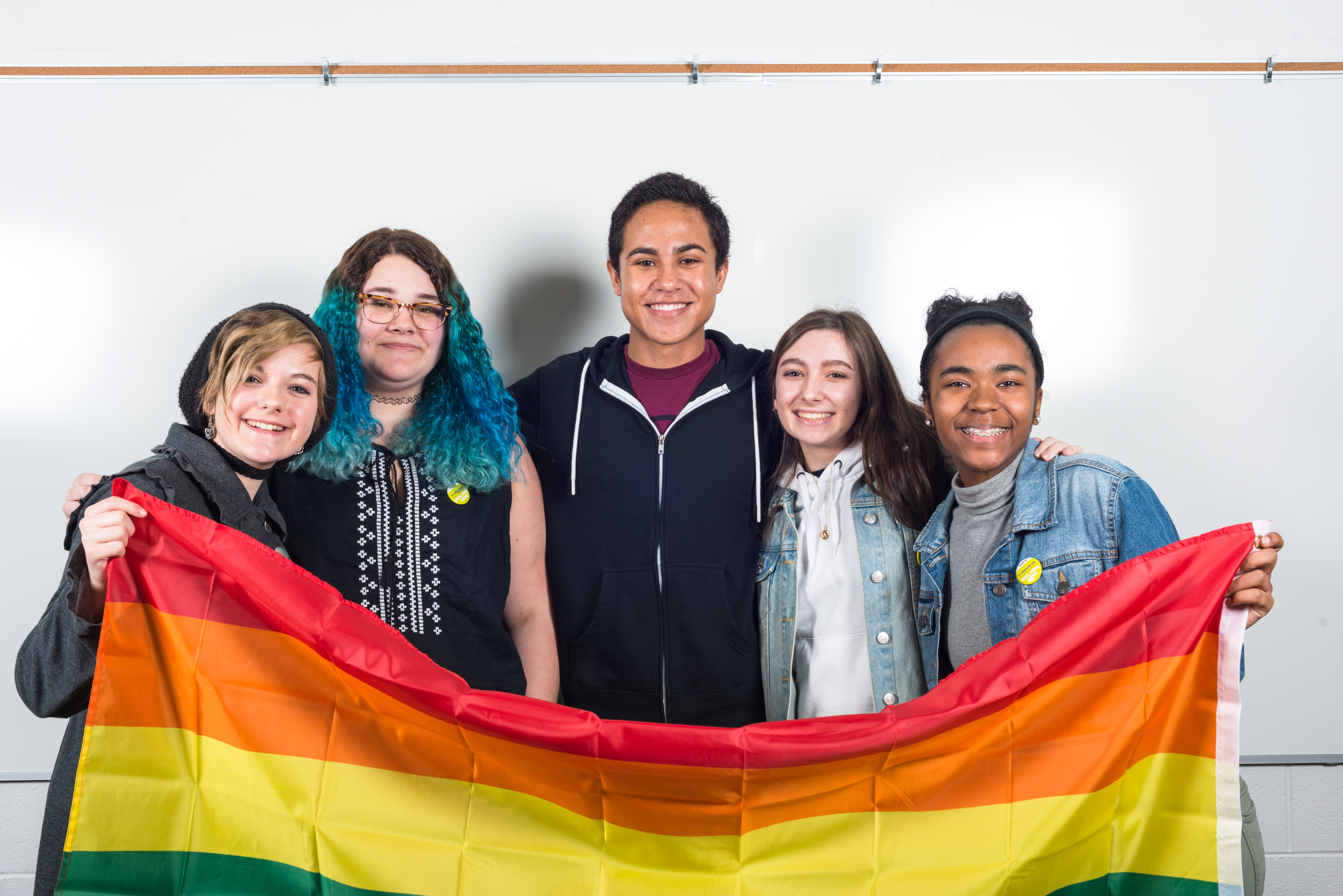 A group of five high school students hold up a rainbow flag and smile at the camera. Two students are wearing GLSEN pronoun pins.