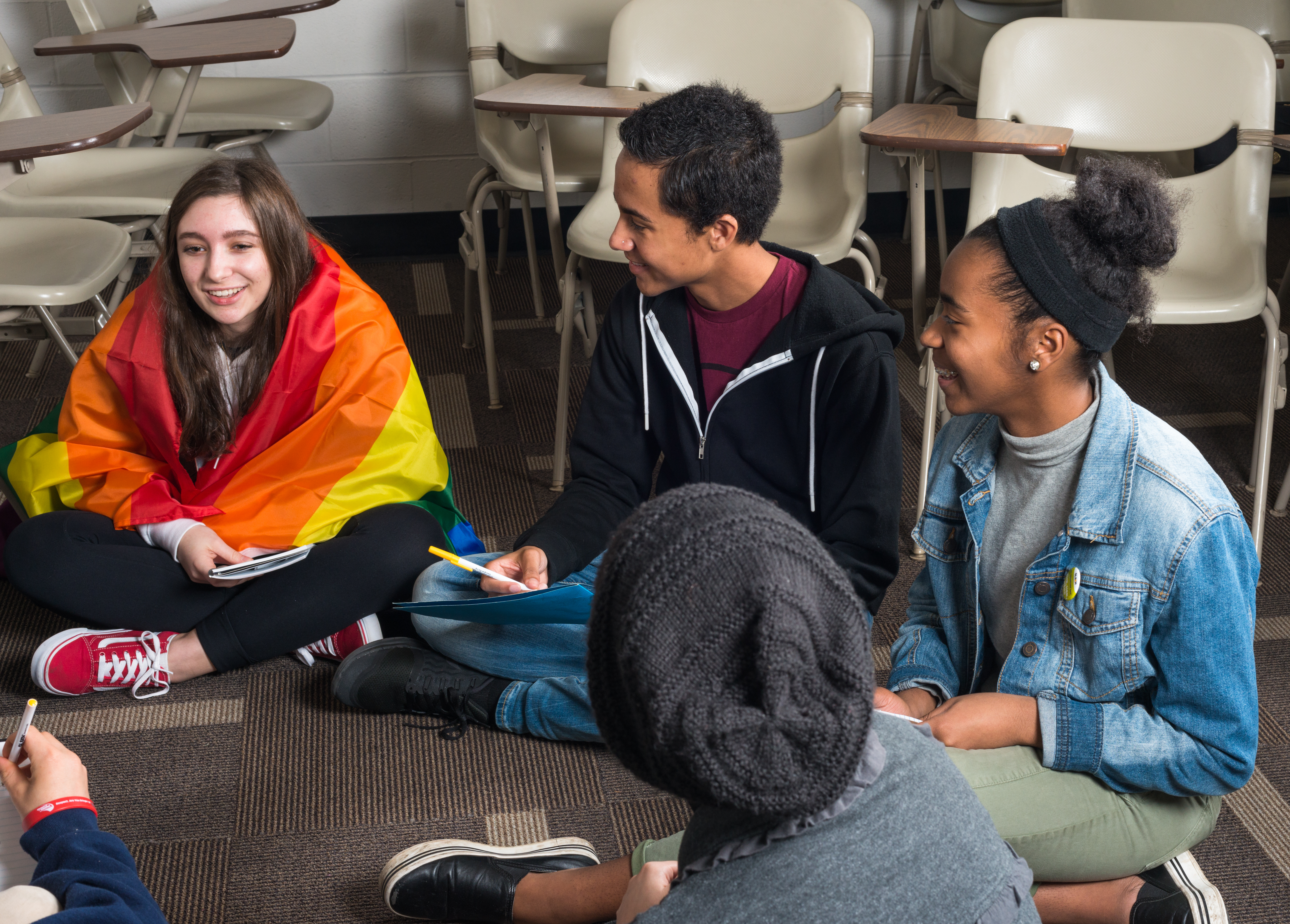 A group of students sit in a circle on the floor of a classroom with the desks pushed aside. They smile and hold notebooks. The first student on the left is wrapped in a rainbow flag.