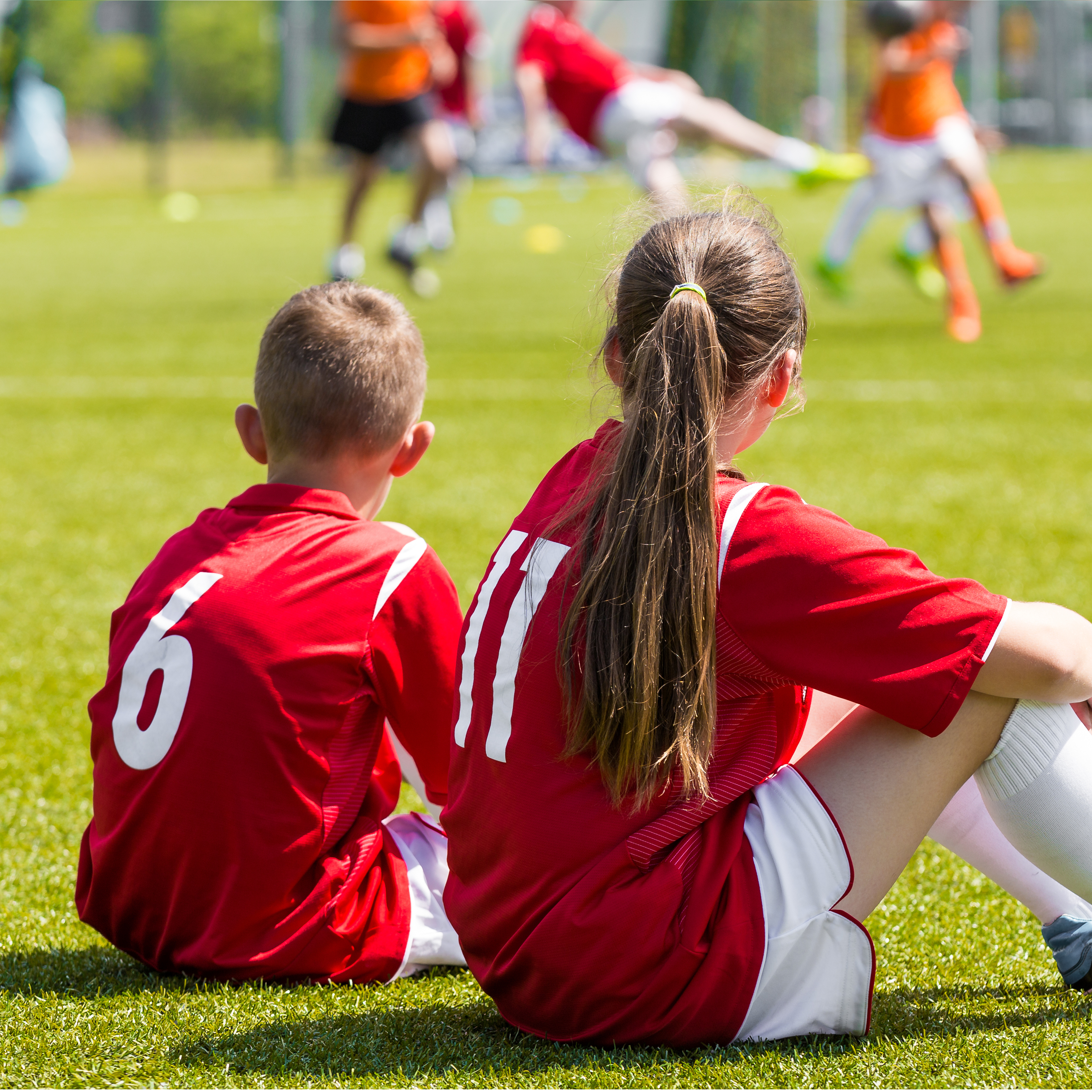 Two soccer players sitting on the grass with their backs to the camera.