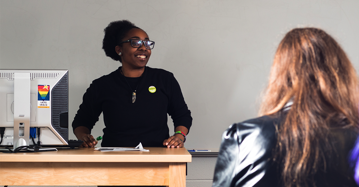A teacher in front of her classroom. She is wearing a pronoun button and her computer has a Safe Space Sticker on it.