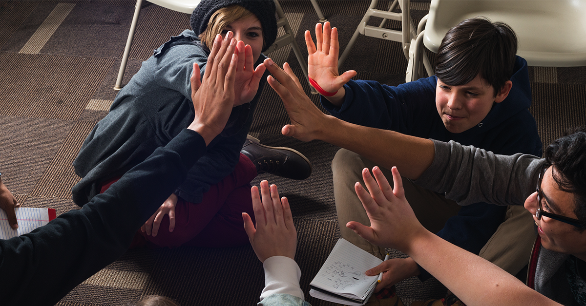 Students high-fiving in a classroom
