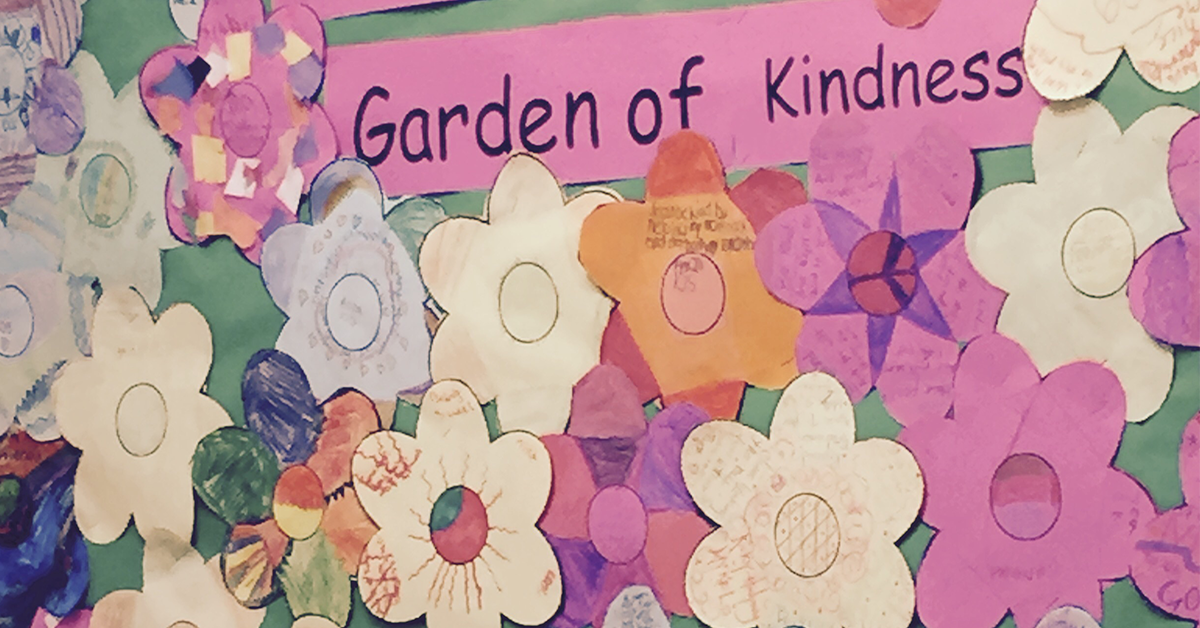 "A wall of cut out flowers that says ""Garden of Kindness"""