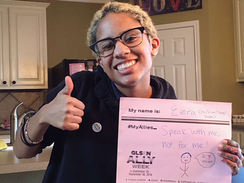 This is a picture of the student holding a sign and a thumbs up. The sign reads: My name is Ezra (He/him/They/Them). My Allies speak with me, not for me!