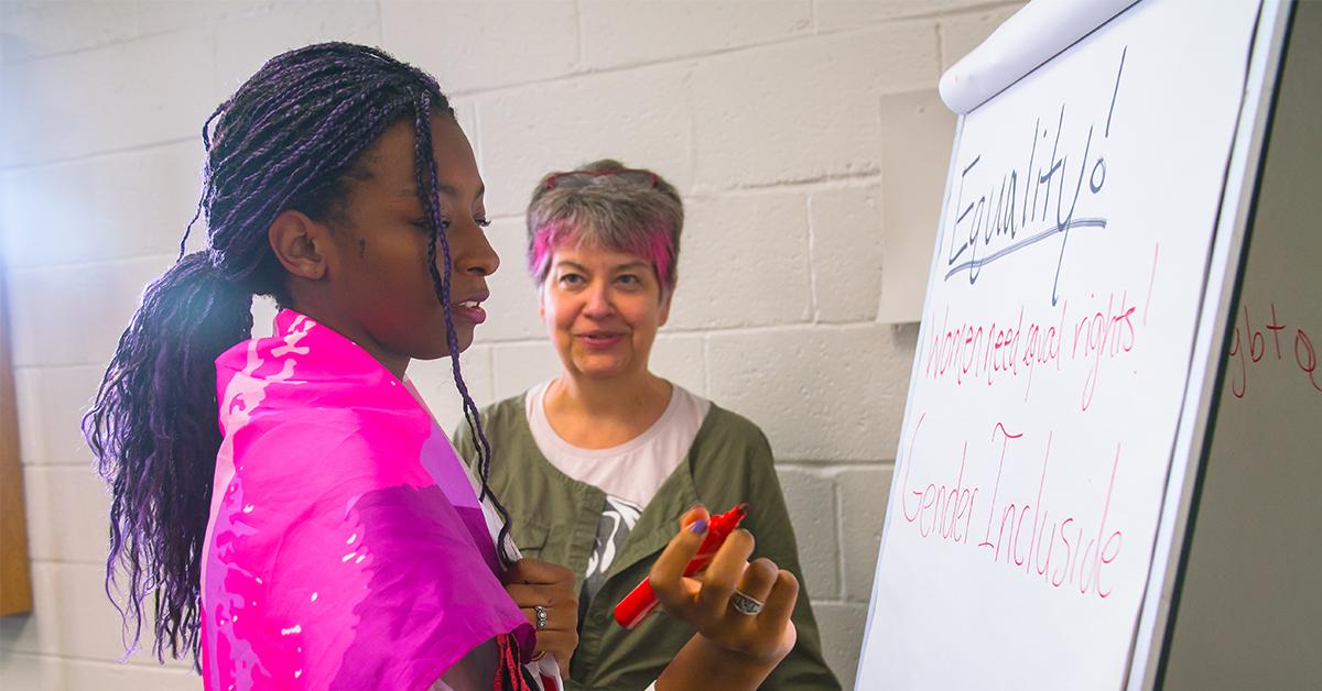 A student and teacher write on a flipchart