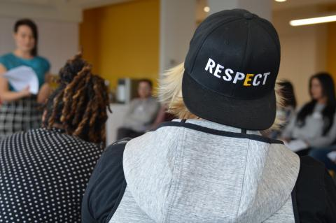 Student facing a speaker. The student is wearing a GLSEN Respect hat.