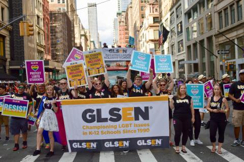A large group of GLSEN volunteers, all wearing black tshirts that say LOVE, holds up posters and a banner as they march in the 2018 NYC Pride Parade. A double-decker bus behind them also has a GLSEN banner and more volunteers on the roof. The banners reads: GLSEN, Championing LGBT Issues in K-12 Schools Since 1990; GLSEN, Creating LGBTQ Inclusive Schools. The posters read: Resist; Protect LGBTQ Students; All Students Deserve Inclusive Schools; Protect Trans Students.