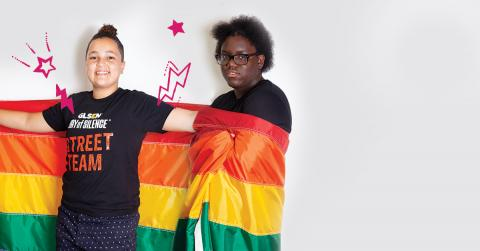 Two National Student Council members, both members of the GLSEN Day of Silence Street Team, stand wrapped in a rainbow flag.