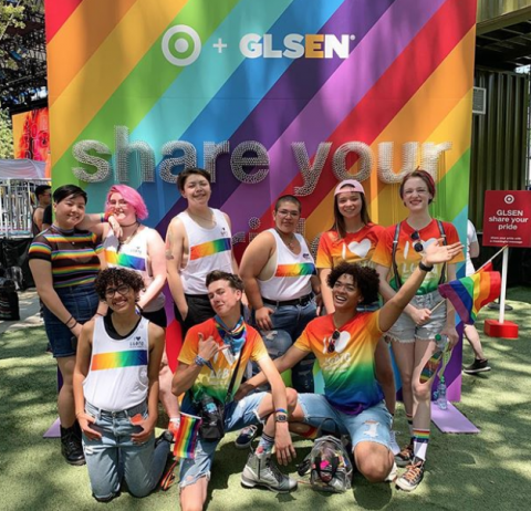 A group of student volunteers, including several National Student Council members, smile and pose in front of a rainbow board at GLSEN's 2019 Share Your Pride event partnered with Target. The students on the left are wearing a white tank-top with a rainbow gradient band and the small text: I Heart LGBTQ. The students on the right are wearing a rainbow gradient t-shirt with the larger text: I Heart LGBTQ.