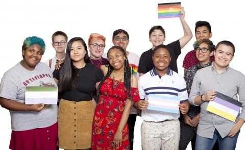 The 2018 National Student Council members stand in a group smiling at the camera in front of a white background. Several hold up print-outs of various pride flags. From left to right, they are: genderqueer, rainbow, trans, and non-binary.