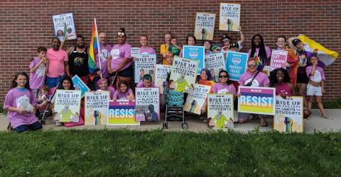 A large group of volunteers and students from GLSEN Omaha smile and hold up rainbow flags and illustrated Rise Up posters. The posters read: rise up to protect immigrant students; rise up to protect Muslim students; rise upt o protect LGBTQ students; RESIST; rise up to protect trans and GNC students; rise up to protect black students; protect trans students; let youth lead.