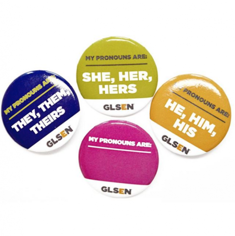 On a white background are four GLSEN pronoun pins. From left to right, the purple one reads: my pronouns are they, them, theirs; the lime one reads: my pronouns are she, her, hers; the gold one reads: my pronouns are he, him, his; and the blank magenta one reads: my pronouns are.