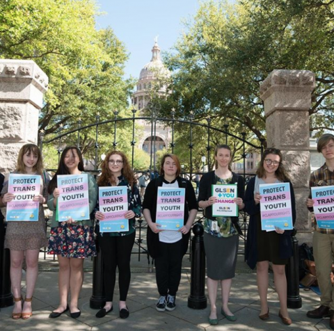 A row of seven students stands in front of a state capital holding GLSEN signs that read: Protect Trans Youth.
