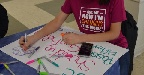 A GLSEN volunteer sits at a table and works on their protest sign for the Washington, D.C. March for Our Lives demonstration. They wear a GLSEN t-shirt that reads: Ask me how I'm changing the world. On the table are a cell phone and several Sharpie markers in various colors.