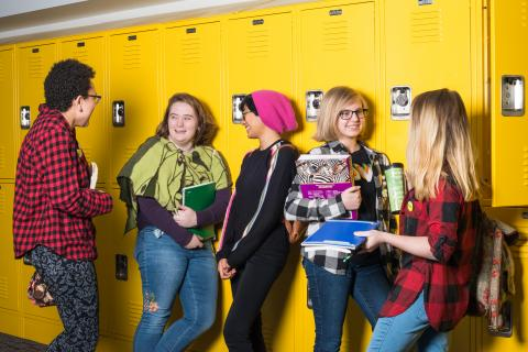 Five high school students carrying backpacks and books lean against bright yellow lockers and amicably talk to each other.