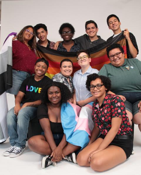 Image is a group of queer students holding the rainbow flag, the trans flag, and the asexual flag.