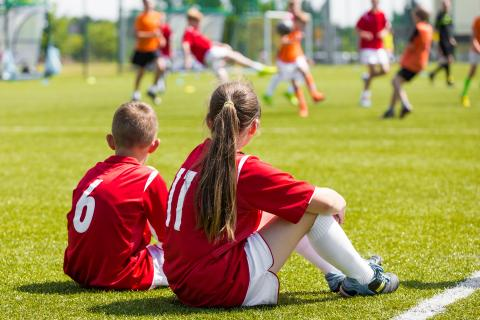 Two students in red soccer jerseys sitting out a soccer game.