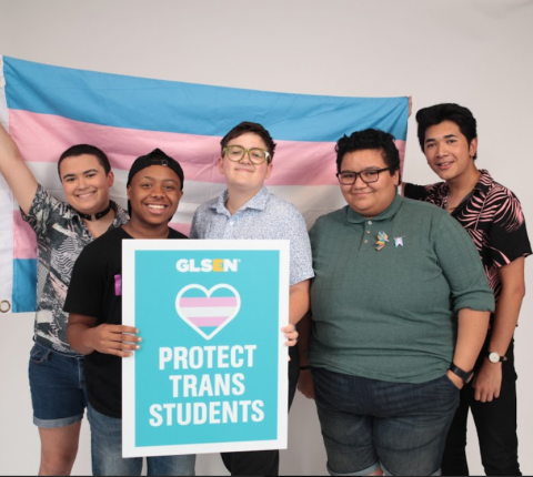 "Five trans youth stand in front of a trans flag, holding a sign that says ""Protect Trans Youth"""