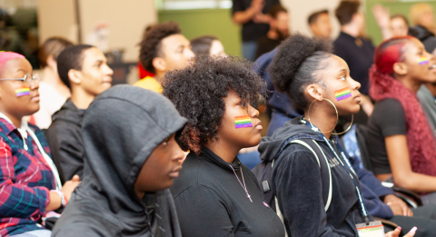 Students sitting at a Day of Silence rally with rainbow stickers on their faces.