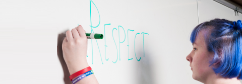 A student writing the word RESPECT on a white board.