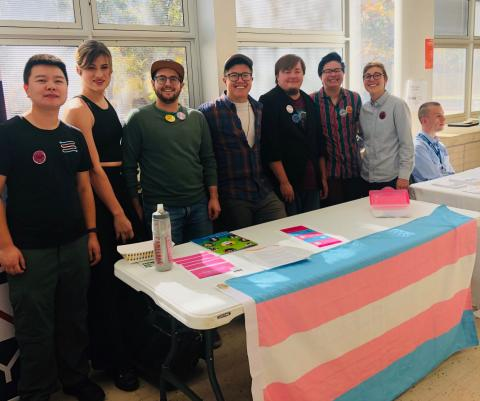 A group of educators stands behind a table that has the trans flag on the front of it.