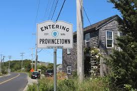"Road sign that reads ""Entering Provincetown"". There is a brown house on the left behind the sign and a road on the right. The sky is blue with no clouds."