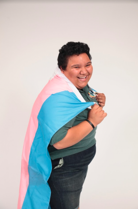 Reggie standing to the side with a trans flag draped over his shoulders.